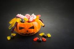 Le potiron Jack avec des sucreries de Halloween worms, les crânes, battes sur le fond noir image stock