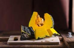 Le potiron thaïlandais cru a coupé la moitié sur la table en bois Photographie stock