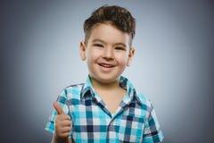 Le pouce heureux réussi d'exposition de garçon de portrait de plan rapproché a isolé le fond gris images stock