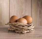 Le poulet eggs dans un nid de corde sur le fond Photos stock
