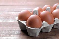 Le poulet eggs dans un plateau pour des oeufs sur un fond en bois brun images stock