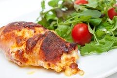 Le poulet enveloppé en lard a servi avec de la salade Image stock