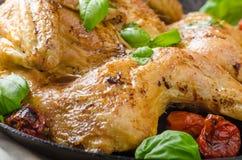 Le poulet a fait cuire au four avec les tomates et le basilic sur la casserole de fer photo stock