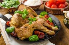 Le poulet a fait cuire au four avec les tomates et le basilic sur la casserole de fer photos libres de droits
