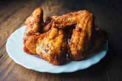 Le poulet frit frais d'un plat blanc a placé sur une table en bois Photographie stock