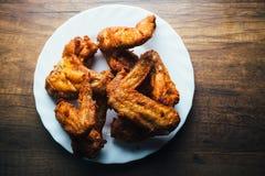 Le poulet frit frais d'un plat blanc a placé sur une table en bois Photos stock
