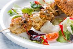Le poulet a grillé la viande sur le bâton avec de la salade et des tomates du plat blanc Fermez-vous avec le foyer sélectif Images libres de droits