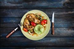 Le poulet rôti avec des légumes et le vert ont écrasé des pommes de terre Fourchette, couteau sur un fond en bois coloré Vue supé photographie stock