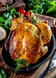 Le poulet rôti avec le romarin a servi du plat noir avec des sauces sur la table en bois, fin  photo stock