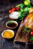 Le poulet rôti avec le romarin a servi du plat noir avec des sauces sur la table en bois, vue supérieure photographie stock
