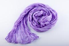 Le pourpre élégant a ridé l'écharpe de mousseline de soie étendue sur le fond blanc Photographie stock