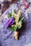 Le pourpre du boutonniere du marié doux se trouve sur un fond en bois image stock