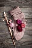 Le pourpre a tricoté des chaussettes avec une boule des nuances de fil de rose Images libres de droits