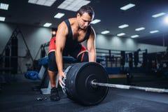 Le powerlifter masculin prépare un barbell dans le gymnase image stock