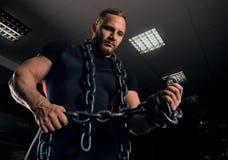 Le powerlifter professionnel se tient dans le gymnase avec des chaînes de fer images stock