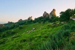 Le pré de haute montagne et le coucher du soleil énorme de roche Photos stock