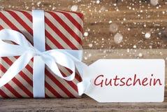 Le présent avec des flocons de neige, texte Gutschein signifie le bon Photographie stock libre de droits