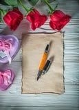 Le présent en forme de coeur en métal enferme dans une boîte la feuille f de papier de vintage de roses rouges Photographie stock