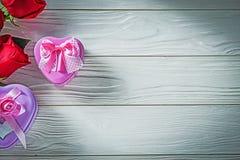 Le présent en forme de coeur en métal enferme dans une boîte les roses rouges les vacances en bois de conseil Image stock