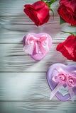 Le présent en forme de coeur en métal enferme dans une boîte les roses rouges naturelles sur le boa en bois Image stock