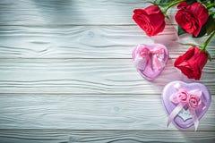 Le présent en forme de coeur en métal enferme dans une boîte les roses rouges naturelles sur le boa en bois Image libre de droits