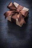 Le présent enfermé dans une boîte a attaché l'arc sur la vue supérieure de panneau en bois de vintage Photo libre de droits
