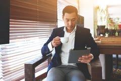 Le Président masculin qualifié lit l'information financière sur le comprimé numérique pendant le repos en café Photographie stock libre de droits