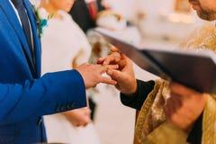 Le prêtre mettant un anneau sur le doigt du marié pendant le mariage traditionnel dans l'église Photo libre de droits