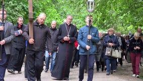 Le prêtre portent la croix en bois par la route de gravier Concept de la douleur de Jesus Christ banque de vidéos