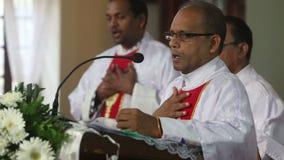 Le prêtre sur le podium souhaite la bienvenue à des paroissiens banque de vidéos
