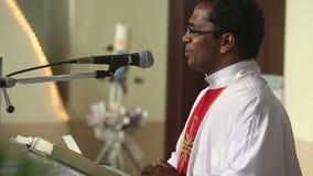 Le prêtre sur le podium souhaite la bienvenue à des paroissiens clips vidéos