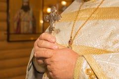 Le prêtre tient un crucifix dans des ses mains photos libres de droits