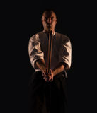 Le practicer Aikidoka d'Aikido avec une épée en bois de formation boken la photo foncée de dojo photographie stock libre de droits