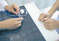 Le praticien prescrit le nouveau médicament à un patient plus âgé photographie stock