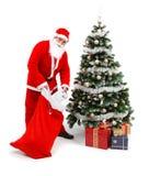 Le père noël mettant des cadeaux sous l'arbre de Noël Image libre de droits
