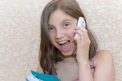 Le pre tonåringflickan som kallar på smartphonen som är utomhus- Fotografering för Bildbyråer