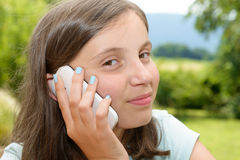 Le pre tonåringflickan som kallar på smartphonen som är utomhus- Arkivfoton