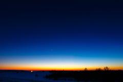 le premier se tient le premier rôle à l'arrière-plan d'un coucher du soleil lumineux Images libres de droits
