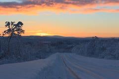 Le premier soleil rayonne sur la route dans la forêt du nord couverte de neige d'hiver après la nuit polaire Photos libres de droits