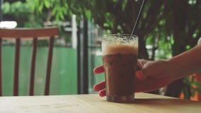 Le prese della ragazza hanno ghiacciato il caffè Latte della bevanda della donna Bevanda fredda sulla tavola archivi video