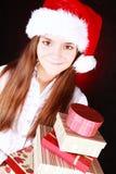 Le presents för julflickaholding över dark royaltyfria bilder