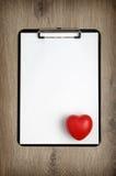 Le presse-papiers avec le livre blanc vide et le coeur forment Photos stock
