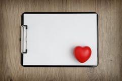 Le presse-papiers avec le livre blanc vide et le coeur forment Photographie stock libre de droits