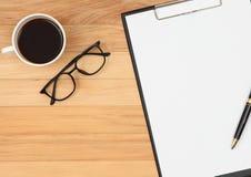 Le presse-papiers avec le stylo, les lunettes et la tasse de café sur le vintage brunissent W photographie stock