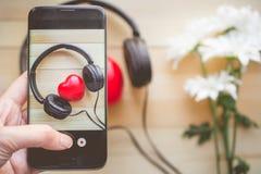 Le pressing de doigt sur le smartphone pour le coeur de photographie écoutent musique Photos stock