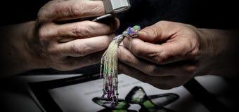 Le priseur expert de bijoux regarde les bijoux avec une loupe photos stock