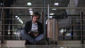 Le problème avec le transport, le retard du vol, l'homme déprimé son bagage et le comprimé, rouge de mal de tête observe Photo stock