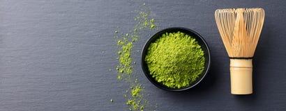 Le procédé de cuisson de thé vert de Matcha dans une cuvette avec le bambou battent Noircissez le fond d'ardoise Copiez l'espace  images libres de droits