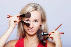 Le procedure di bellezza, donna tiene le spazzole di trucco vicino al fronte. Immagine Stock
