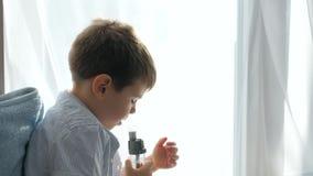 Le procedure mediche, bambino facente male respira attraverso il tubo dell'inalatore per la seduta respirante della difficoltà de stock footage